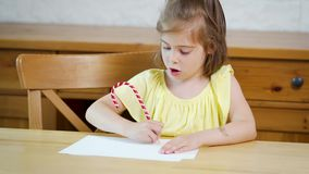 Little girl in a yellow dress with a pencil draws on paper. On a wooden table stock video