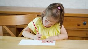 Little girl in a yellow dress with a pencil draws on paper. On a wooden table stock video footage