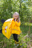 Little girl in a yellow dress with   umbrella Royalty Free Stock Image