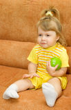Little girl in yellow eat  green apple Royalty Free Stock Photography