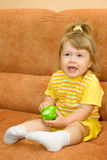 Little girl in yellow eat green apple Stock Images