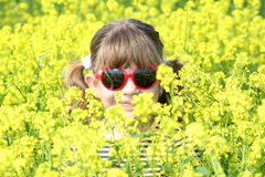 Little girl in yellow flowers field Stock Images