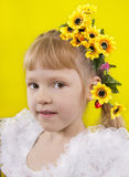 The little girl with yellow flowers in hair. Stock Photo