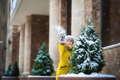 A little girl in a yellow jacket plays with snow in the winter. The child hides behind a Christmas tree and throws snow on the cam. Era Royalty Free Stock Photography