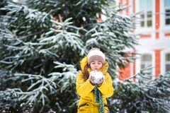 A little girl in a yellow jacket plays with snow in the winter. The child holds the snow in his hands. And blows on it Stock Photo