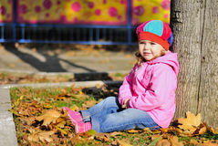 Little girl with a yellow leaflet in autumn park Stock Photo