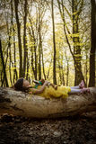 Little girl in yellow princess dress laying on tree Royalty Free Stock Photos
