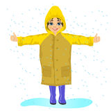 Little girl in yellow raincoat in the rain. Stretching her arms to the sides Stock Photo