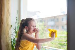 Little girl in shirt and blue shorts washes the windows at home. Daughter with a cat wash the window stock images
