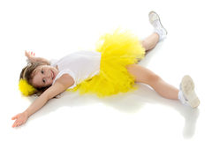 The little girl in the yellow skirt lying on the floor. royalty free stock image