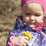 Little girl with yellow spring flowers. A little girl sees a bunch of yellow spring flowers Stock Photos