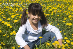 Little girl in yellow spring meadow Stock Photo