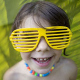 Little girl in yellow sun glasses Stock Images
