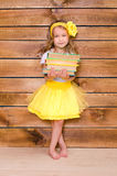 Little girl in yellow tutu with stack of books Stock Images