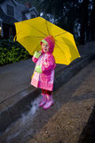 Little girl with yellow umbrella playing in rain 2 Royalty Free Stock Photography
