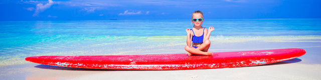 Little girl in yoga position meditating on Stock Photos