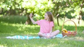 Little girl in yoga position in the park. Little girl takes selfie by smartphone in the spring park stock video footage