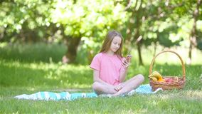 Little girl in yoga position in the park. Little girl talks by smartphone in the spring park stock video