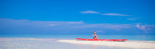 Little girl in yoga position on surfboard at Royalty Free Stock Photos