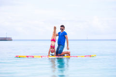 Little girl and young dad have fun on surfboard Stock Photography