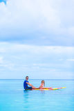 Little girl and young dad have fun on surfboard Royalty Free Stock Images