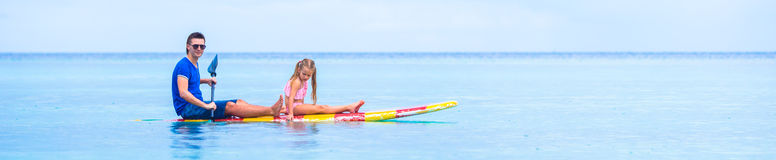 Little girl and young dad have fun on surfboard Royalty Free Stock Image