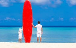 Little girl and young dad with surfboard during Royalty Free Stock Photo