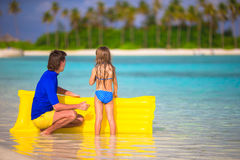 Little girl and young father with air mattress on Royalty Free Stock Images