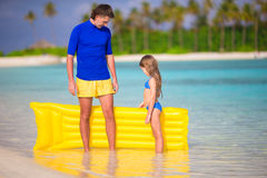 Little girl and young father with air mattress on Royalty Free Stock Image