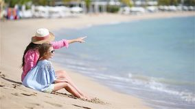 Little girl and young mother during beach vacation. Beautiful mother and her adorable little daughter at beach stock video footage