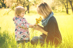 Little girl and young mother enjoying spring field dandelion flo Stock Photos