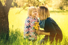 Little girl and young mother enjoying spring field dandelion flo Stock Photo
