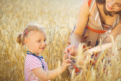 Little girl with young mother at grain wheat field Stock Photo