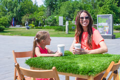 Little girl and young mother at outdoor cafe on Stock Photo