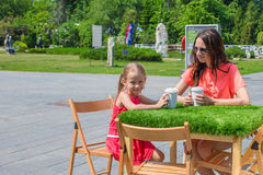 Little girl and young mother at outdoor cafe on Royalty Free Stock Images