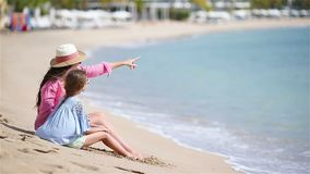 Little girl and young mother on white beach. Beautiful mother and her adorable little daughter at beach stock footage