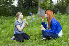 Little girl and young woman blowing soap bubbles Stock Image