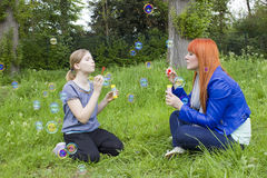 Little girl and young woman blowing soap bubbles Royalty Free Stock Image