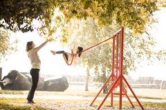 Little girl and young woman on the playground Stock Photos