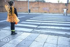 Little girl at zebra crossing in halloween costumes towards chil. Badajoz, Spain - October 27, 2017: Little girl at stopped at zebra crossing in halloween stock photography