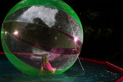 Little girl in Zorb in the pool Royalty Free Stock Photos