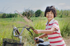 Little girle with bicycle in countryside Royalty Free Stock Photography