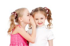 Little girlfriends sharing a secret. Isolated on a white background royalty free stock image
