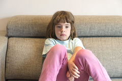 Little girll watching TV. Little girl watching TV sitting on the couch Stock Photo