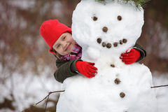 Little girlposing with snowman Royalty Free Stock Images