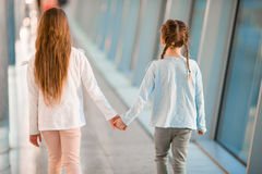 Little girls in airport near big window inside while wait for boarding Stock Images