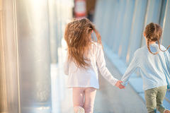 Little girls in airport while wait for their flight Stock Photo