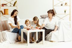 Little girls, attractive young mother and charming grandmother are sitting at home stock photography
