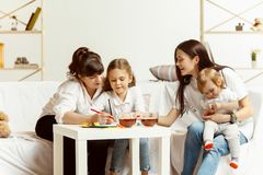 Little girls, attractive young mother and charming grandmother are sitting at home stock photo