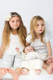 Little girls and a baby boy in white clothes sitting royalty free stock image